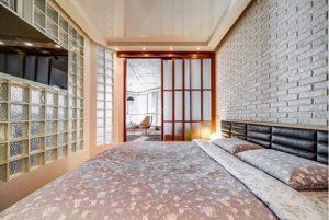 Dormitorio de loft con paredes de pavés