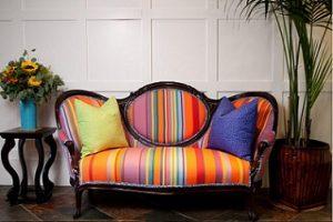 Sofá antiguo tapizado en tela de rayas multicolores