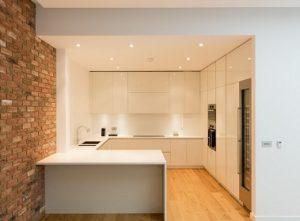 Cocina blanca sin tiradores abierta al salón