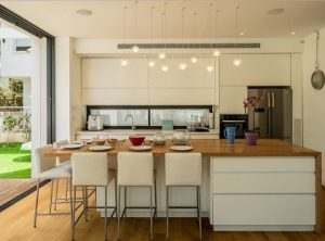 Cocina integrada en el salón con gran isla central de roble