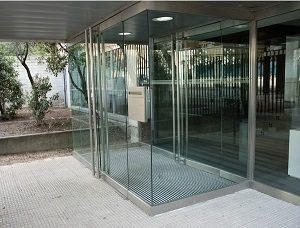 Felpudo metálico entre paneles de vidrio en edificio de oficinas
