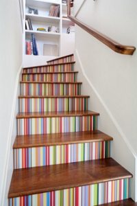 Escalera decorada con papel pintado multicolor en las tabicas de los escalones