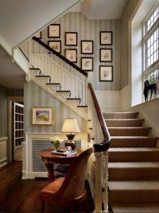 Escalera con papel pintado de rayas y friso de madera lacada