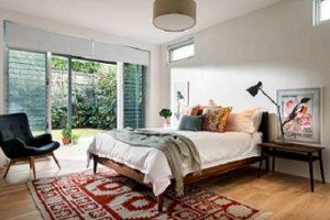 Alfombra oriental en dormitorio con mobiliario nórdico