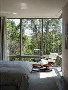 Pared acristalada con cortinas en barra en dormitorio