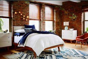 Persianas venecianas en dormitorio con paredes de ladrillo