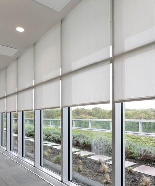 Estores enrollables en muro cortina con cortinero