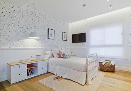 Habitación infantil con friso de madera y papel pintado de topos